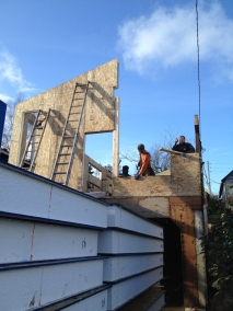 Structural insulated panels (SIPS) are stacked up, waiting to be fit together. Photo by Becky Chan.