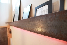A steel beam required for retrofitting the structure becomes an art shelf and lighting element at the entry.