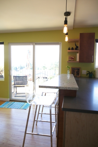 Sliding glass doors at the kitchen bar open to the deck beyond.