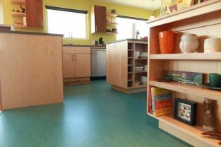 Maple veneer plywood cabinets and vibrant marmoleum floor.