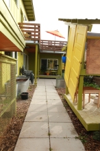 A view of the backyard, with chicken coop on the left and playhouse on the right.