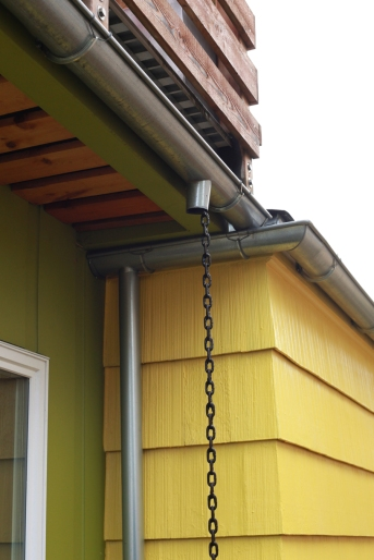New meets old, with galvanized half round gutters and rain chain.
